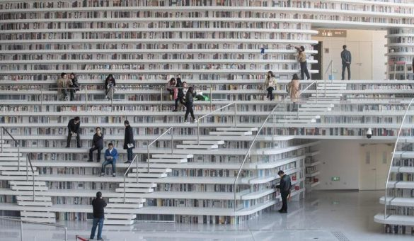 This picture taken on November 14, 2017 shows people visiting the Tianjin Binhai Library. A futuristic Chinese library has wowed book lovers around the world with its white, undulating shelves rising from floor to ceiling, but if you read between the lines you'll spot one problem. Those rows upon rows of book spines are mostly images printed on the aluminium plates that make up the backs of shelves. / AFP PHOTO / FRED DUFOUR / To go with AFP story China-library-architecture, FOCUS by Becky Davis